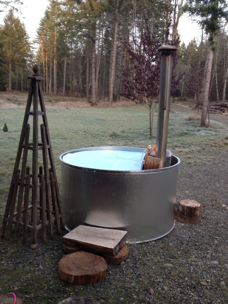 With a hand-crafted log step and a garden obelisk towel hanger, we are ready to soak.